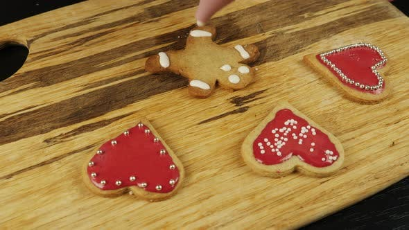 Decorated gingerbread man with white glazing. Female hand is decorating cookie