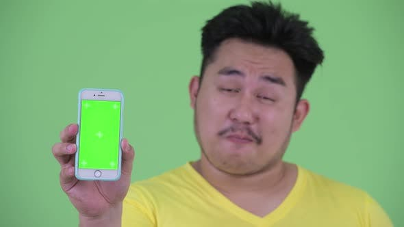 Thumbnail for Face of Happy Young Overweight Asian Man Showing Phone