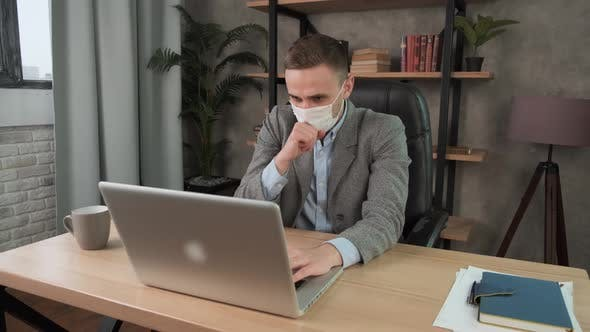 Thumbnail for Young Businessman Coughs Into Protective Face Mask Working in the Office. Caucasian Man with Acute