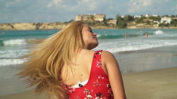 Thumbnail for Frau mit blondem Haar steht mit ihrem Rücken zur Kamera, dann dreht sich, Ihr Haar flattert in langsam
