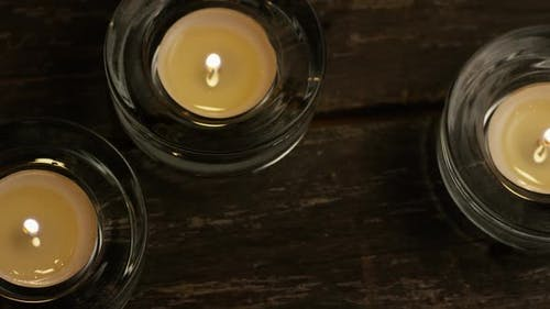 Tea candles with flaming wicks on a wooden background