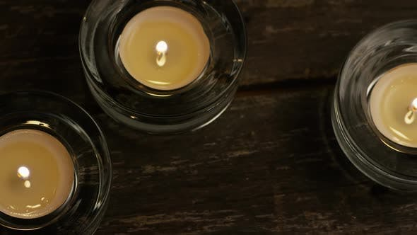 Thumbnail for Tea candles with flaming wicks on a wooden background