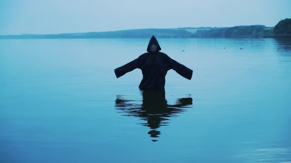 Thumbnail for Böse Hexe in einem schwarz Kapuze in der fluss