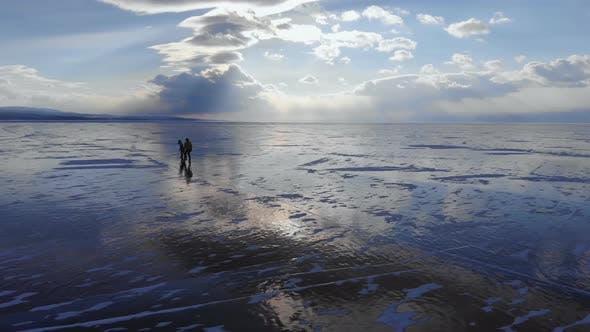 Thumbnail for Ein junges Paar von Reisenden Skate auf dem Eis des Eisgefrorenen Endlosen Sees