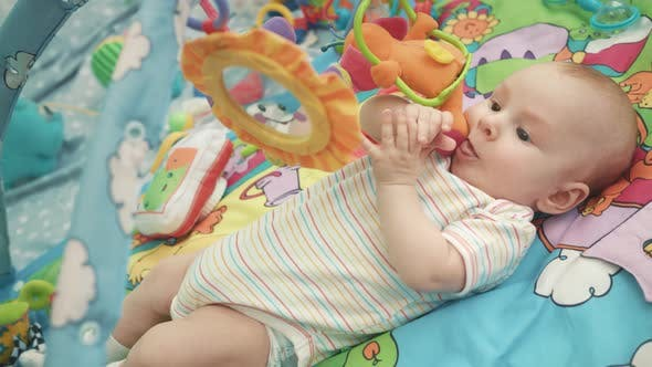 Thumbnail for Infant Baby Playing on Colorful Mat. Close Up of Cute Baby Boy Play with Toy