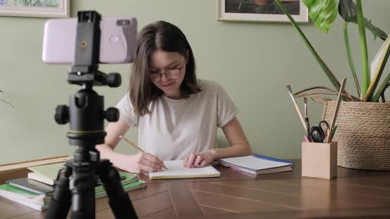 Thumbnail for Teenager Girl Studying Online Using Smartphone, Listening and Talking at Video Conference