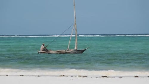 African Fisherman on an Old Dry Wooden Boat Sail in Ocean at High Tide Zanzibar