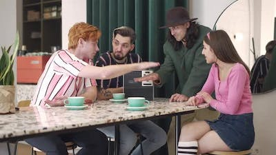 Young Friends Stacking Hands in Retro Coffee Bar Smiling