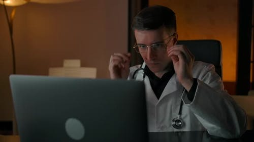 The Doctor Puts on Glasses and Communicates with the Patient Online at Home in the Evening