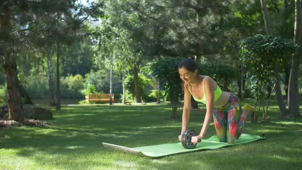 Thumbnail for Smiling Fit Woman Working Out with Ab Roller in Park