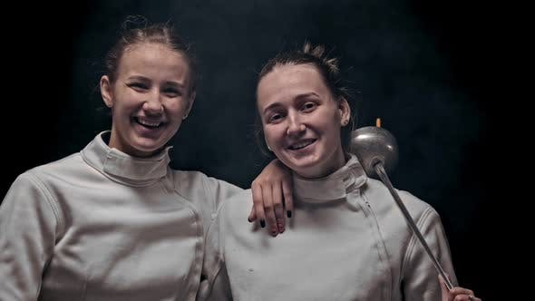 Thumbnail for Two Young Women Fencers Standing in the Studio and Looking in the Camera