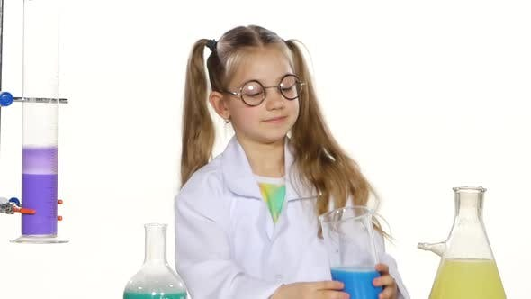 Thumbnail for Cute Girl with Ponytails in Uniform and Round Glasses Evaluates, Standing By the Table Chemical