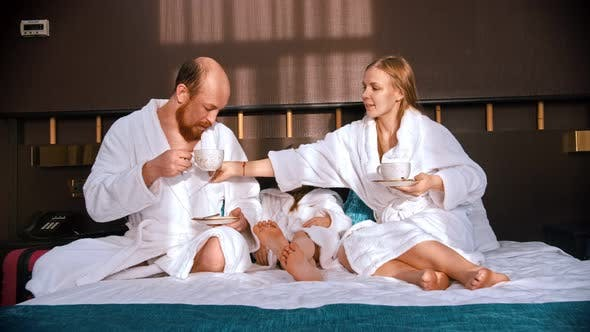 Thumbnail for A Successful Family in White Bathrobes Sitting in the Hotel Bed and Drinking Tea