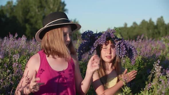 Verspielte Freundinnen tanzen auf Lupinfeld in der Sommerlandschaft. Fröhliches Mädchen Tanzen für Soziale