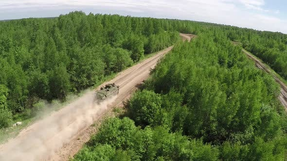 Flying Over Military Vehicle on Dirt Road in Woodland