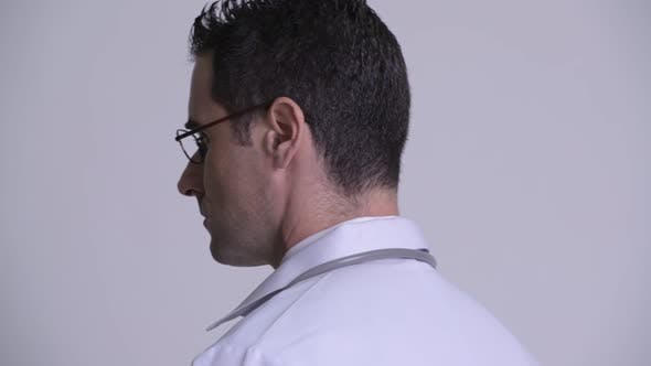 Thumbnail for Rear View Head Shot of Handsome Man Doctor Looking Back and Removing Eyeglasses