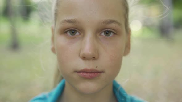 Thumbnail for Close-up Portrait of a Young Blond Girl Looking at the Camera. Pretty Caucasian Teen Standing in the
