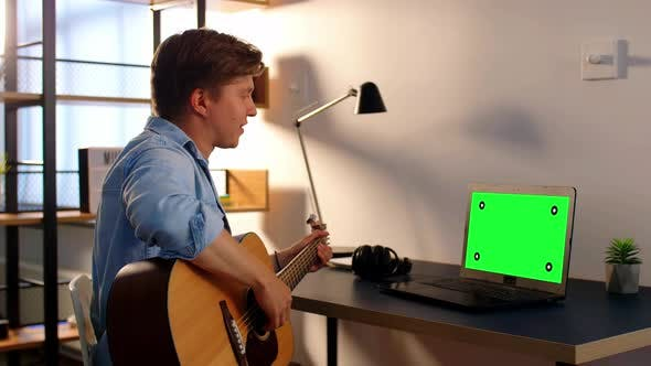 Young Man with Laptop and Guitar Having Video Call