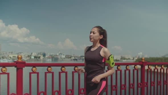 Thumbnail for Sportliche Frau zu Fuß schnell auf Brücke nach dem Joggen