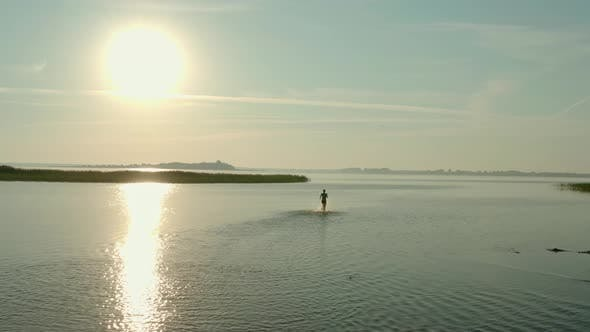 Thumbnail for Aerial Drone View, Attractive Young Woman Run in a Lake at Summer Day.