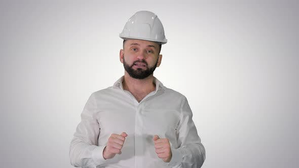 Thumbnail for Engineer in a White Helmet Explaining Something To Camera on Gradient Background