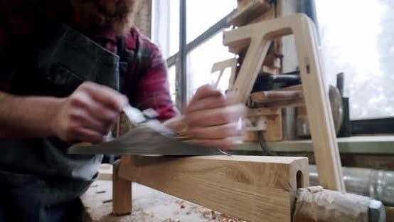 Der Tischlermeister mit einem Planer bei der Arbeit in der Werkstatt