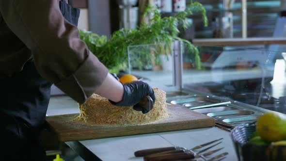 Thumbnail for Bakeries, a Professional Female Chef in Gloves Cut Freshly Baked Dessert Cake with Knife on Cutting