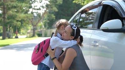 Mother Hugging Daughter Before School Outdoors