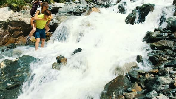 Thumbnail for Man Carries a Woman with a Backpack Over a Mountain Stream on Her Back Barefoot Into a Ford