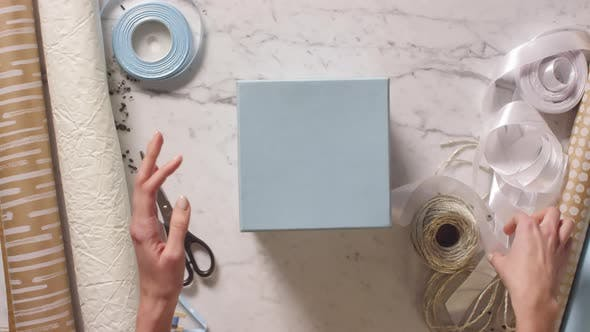 Thumbnail for Woman Packing Old Fashioned Camera into Gift Box and Tying a Bow