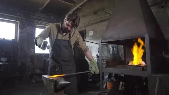 Thumbnail for Blacksmith Treating Metal in Smithy