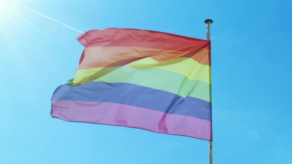 Thumbnail for Big Rainbow Flag Gay Pride LGBTQ Developing By the Wind Against the Blue Sky.