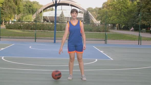 Porträt eines jungen Mädchens Basketballspieler Steht mit dem Ball und Blick auf die Kamera.  Ein