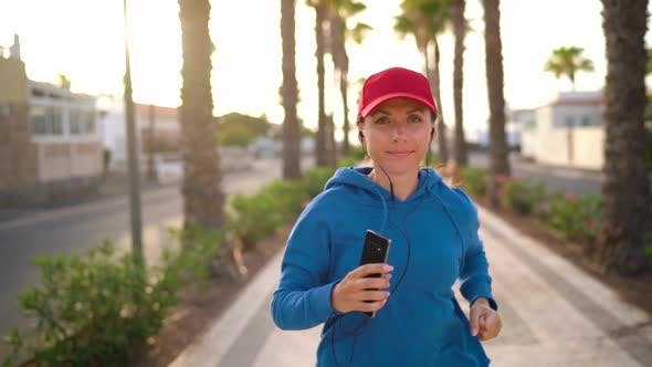Thumbnail for Woman with Headphones and Smartphone Runs Down the Street Along the Palm Avenue at Sunset. Healthy