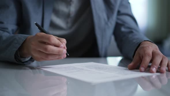 A Man Signs a Document