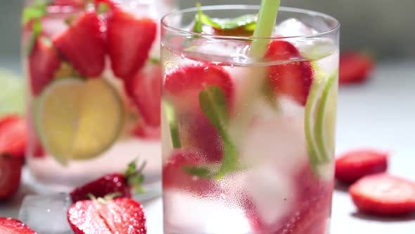 Detox sassy water with strawberries and lime in glasses.