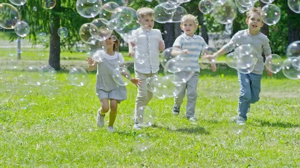 Cover Image for Happy Children Running through Lots of Soap Bubbles