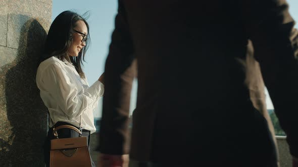 Slow Motion of Beautiful Asian Businesswoman Using Smartphone Standing Outdoors Near Office Buiding