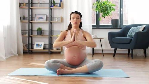 Pregnant Woman Meditating in Lotus Pose at Home