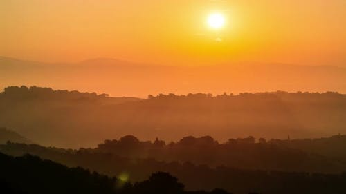 Sunrise time lapse over hills and mountains