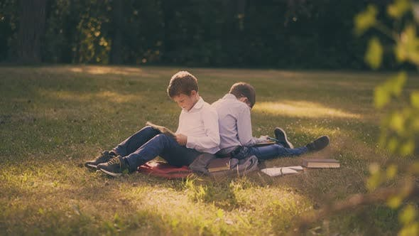 Schoolboys Read Books Doing Home Task on Lush Grass in Park