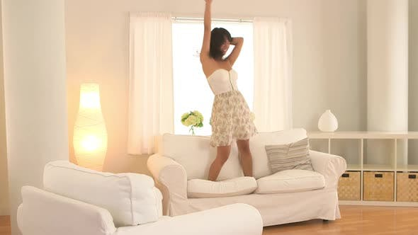 Thumbnail for Asian woman jumping on couch and dancing in living room