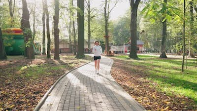 Woman in Activewear Running at Park