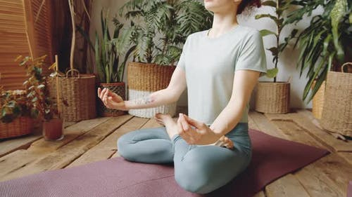 Midsection of Woman Sitting in Lotus Pose and Holding Hands in Mudras