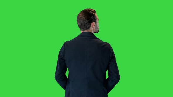 Confident Businessman Standing with Hands on Hips Looking Around on a Green Screen Chroma Key