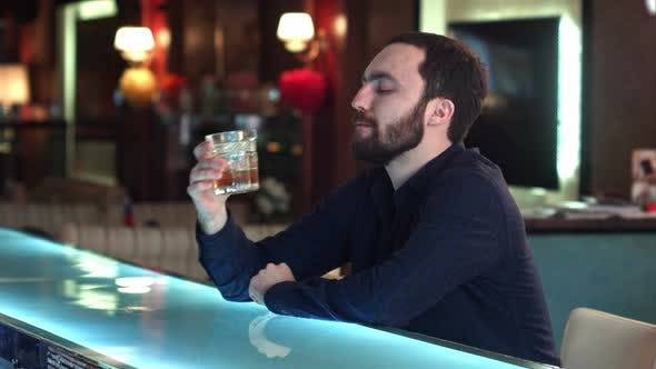 Thumbnail for Handsome Pensive Guy Is Looking Forward and Thinking While Sitting at the Bar Counter in Pub