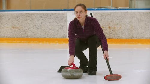 Curling Training on Ice Rink - a Young Woman Pushing the Stone on the Rink with a Brush