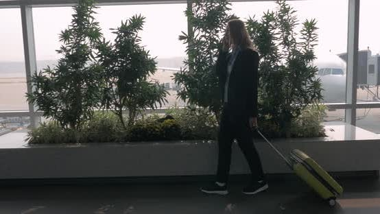 Thumbnail for Woman with Suitcase Talking on Phone and Walking in Airport Terminal