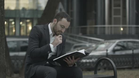 Man in Suit Reading Business Plan with Interest, Sitting on a Bench in Park and
