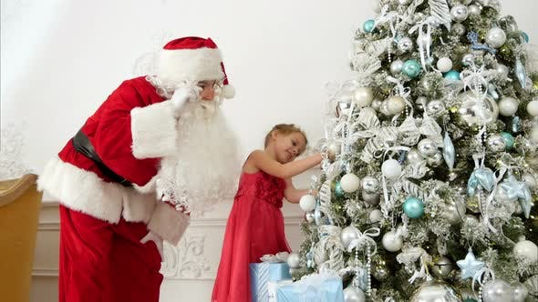 Thumbnail for Santa Claus Helping Pretty Little Girl To Decorate Christmas Tree